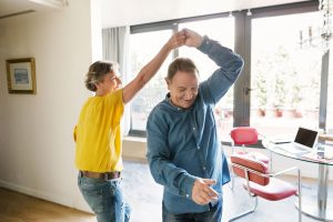 Mature couple dancing in living room.