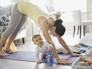 Mom exercising with baby in the living room.