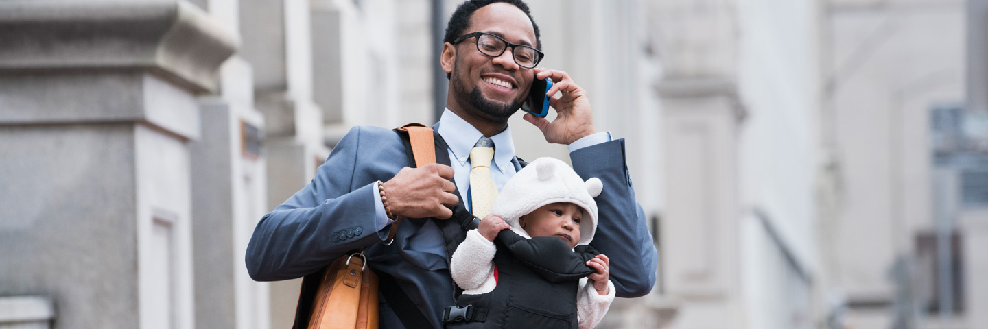 Man talking on phone holding baby in the city.