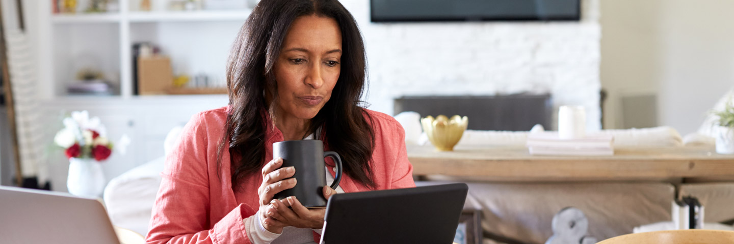 Woman drinking coffee while reading on a computer